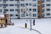Basketball court winter small children nannies — Stock Photo
