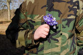 Soldier camouflage hand violet flowers girlfriend — Stock Photo