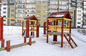 Playground wooden red houses swing rope winter — Stock Photo