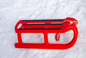 Plastic red sleigh with black rim yard in winter — Stock Photo