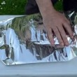 Fast hands wrap big fish into foil for baking in fire ember — Stock Video