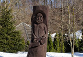 Rural wooden carved man statue snow winter park — Stock Photo