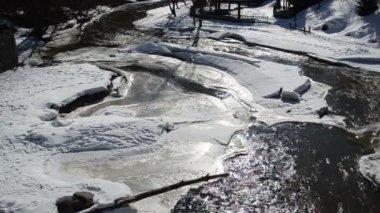Sol reflektioner delvis frozen river vatten snö is vinterdag — Stockvideo