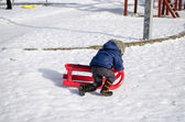 Boy with blue jacket knelt down to red sleigh — Stock Photo
