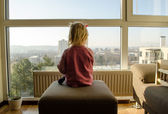 Girl pink sweater sit settee before large window — Stock Photo