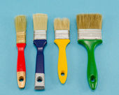 Hand paint brush color different size on blue — Stock Photo