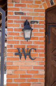 Wc toilet sign symbol red brick wall retro lamp — Stock Photo