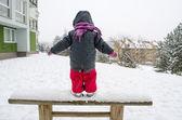 Ребенок с красным брюки стоя деревянная скамья снега — Стоковое фото