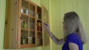 Woman cabinet canned food — Stock Video