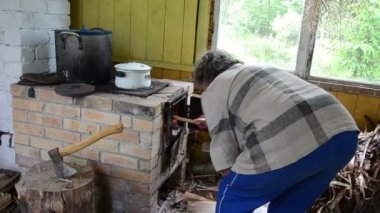 Woman wood stove kitchen — Stock Video