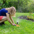 Girl turns garden watering at flower seedling — Stock Photo #45445085