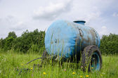 Blue water cistern drink for farm animal in meadow  — Stock Photo