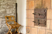 Old rustic furnace doors and wooden rest chair  — Stock Photo