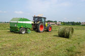 Tractor bailer collect hay in agriculture field  — Foto Stock