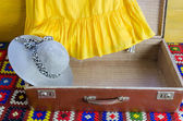 Gray femalee hat suitcase yellow dresses fragment — Stock Photo