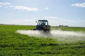 Tractor spray fertilize field pesticide chemical  — Stock Photo