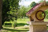 Wooden handmade well in summer garden  — Zdjęcie stockowe