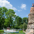 Stone brick lighthouse in summer park on blue sky — Stock Photo #47250793