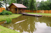 New rural bathhouse and pond with plank footbridge  — Stock Photo