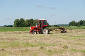 Tractor ted hay dry grass in agriculture field  — Stock Photo