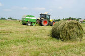 Tractor bailer collect hay in agriculture field  — Stockfoto