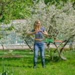 Girl turning hula hoop between flowering cherry — Stock Photo #47575521