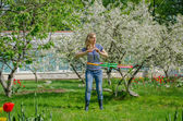 Girl turning hula hoop between flowering cherry   — Stock Photo