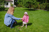 Mother sits in meadow daughter gather daisies  — Stock Photo