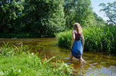 Blond girl blue mottled dress wade flowing river   — Stockfoto