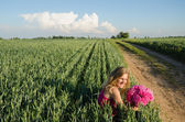 Long rural path and woman sits with peony flower — Stock Photo