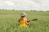 Country girl in dress play guitar wheat field  — Stock Photo