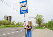 Woman at bus stop with pole tags driving schedules  — Stockfoto