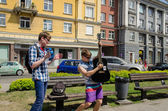 Active buskers with guitars and bell city street   — Stock Photo