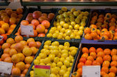 Fresh orange lemon persimmon in plastic boxes   — Stock fotografie