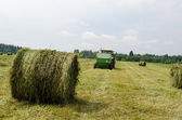 Straw bales agricultural machine gather hay  — Stok fotoğraf