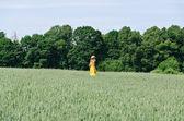 Farmer woman in yellow dress walk wheat field — Stock Photo