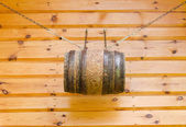 Gable of wooden rural house and barrel with chains  — Stock Photo