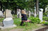 Sorrow woman shrinked near father husband grave  — Stock Photo