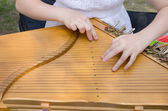 Ancient stringed baltic psaltery and girls hands  — Photo