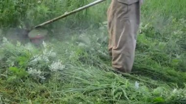 Turn view man with cutter tool mow weeds — Stockvideo