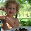 Foto Stock: Portrait of little boy eating in garden