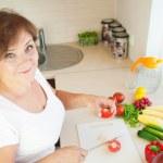 Older woman in kitchen preparing healthy food — Stock Photo #36409925