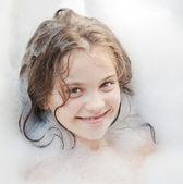 Küçük güzel bir kız bir köpüklü bir duş alıyor — Stok fotoğraf