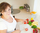 Older woman in kitchen preparing healthy food — Stock Photo