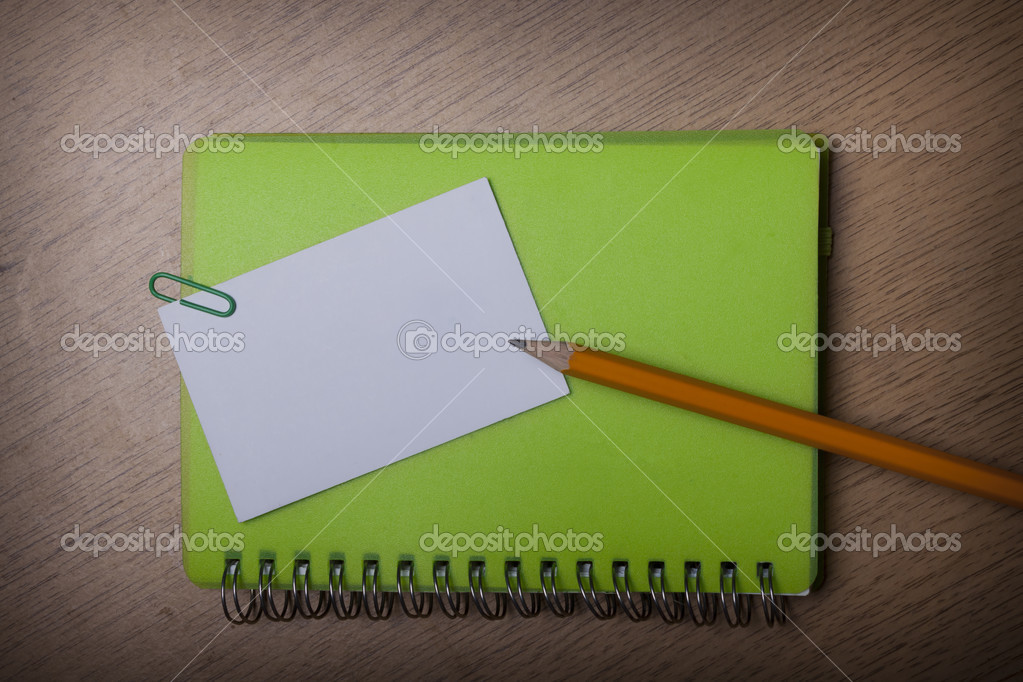 Green notebook on a wooden desk — Stock Photo #13086710