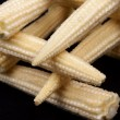 Baby corn on black background — Stock Photo
