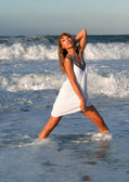 Woman in white dress posing on the sea coast — Stock Photo