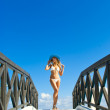 Sexy woman in white bikini standing on small bridge in sunny day — Stock Photo