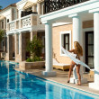 Pretty white bikini girl walking near pool. Greek style — Stock Photo #27290081