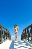 Sexy woman in white bikini standing on small bridge in sunny day — Stock Photo